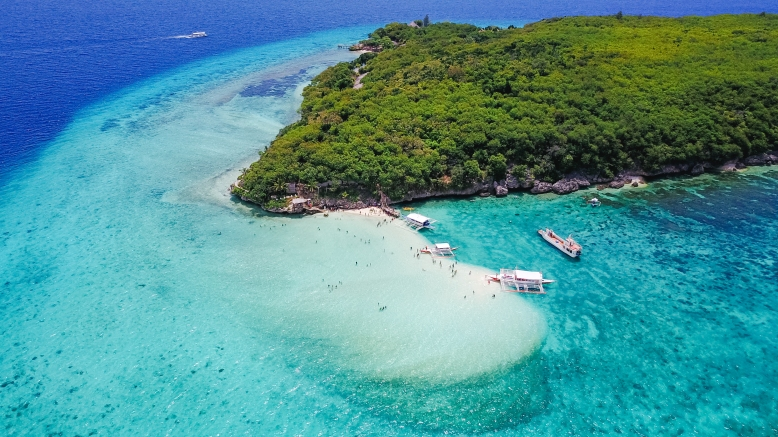 Aerial view of sandy beach with tourists swimming in beautiful c